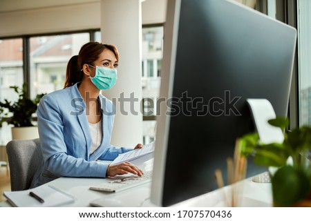 Female entrepreneur wearing face mask while analyzing business reports and working on desktop PC in the office.  Royalty-Free Stock Photo #1707570436