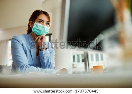 Low angle view of businesswoman with face mask working on desktop PC in the office.  #1707570445
