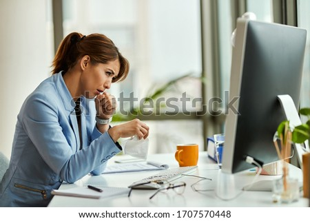 Young businesswoman feeling sick and coughing while working on a computer in the office.  #1707570448