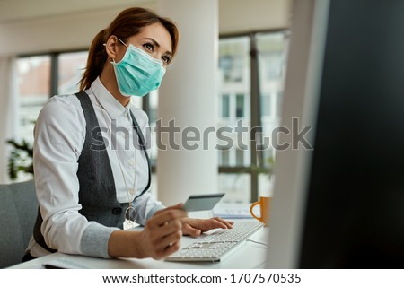Businesswoman with face mask using computer and shopping on the internet with credit card in the office during COVID-19 pandemic.  Royalty-Free Stock Photo #1707570535