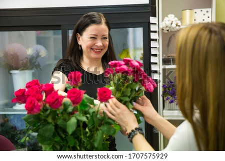 the seller in the flower shop sells a bouquet of flowers to the buyer #1707575929