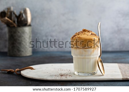 Dalgona coffee or whipped instant coffee. New popular food and drink trend. Light background, one glass with copy space Royalty-Free Stock Photo #1707589927
