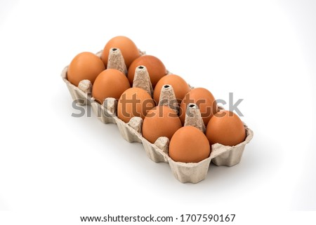 Chicken eggs in cardboard egg box on white background. Raw chicken eggs in open egg box on a white background. Eggs in the package. #1707590167