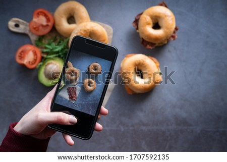 Woman's hand with a mobile phone taking a picture to a salmon bagel and a bacon bagel on concrete background.