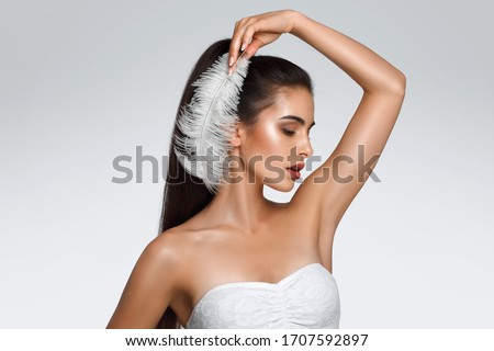Portrait of attractive Caucasian woman with raised hand. beautiful young girl holds feather in hands and looks at armpit. Smooth clean skin of the face and body. concept care, epilation armpit Royalty-Free Stock Photo #1707592897