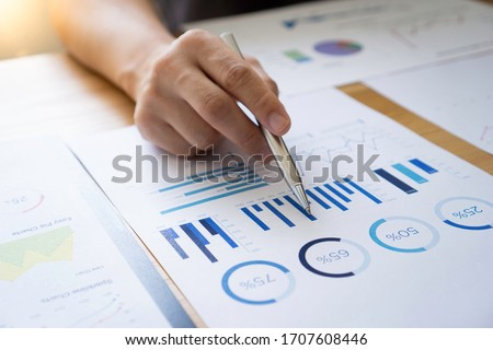 Asian male finance staff Is explaining the performance from the company's rapidly growing bar graph this year. To his boss On the desk at the office, Finance concept Royalty-Free Stock Photo #1707608446