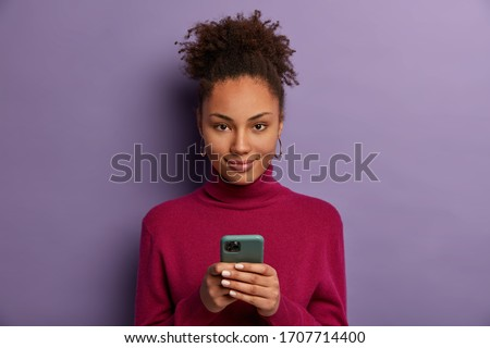Photo of pleased dark skinned millennial girl holds mobile phone, waits for call, texts with friend in online chat, uses special application, taps smartphone screen, checks newsfeed, browses internet #1707714400