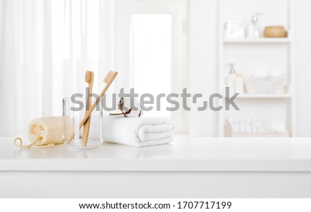 Morning hygiene products on white table top of defocused bathroom #1707717199