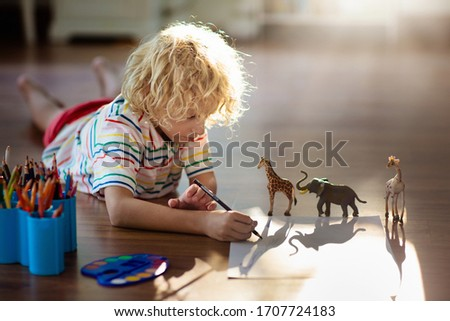 Child shadow drawing animals. Kids play at home. Fun crafts for kindergarten children. Little boy painting giraffe and elephant in sunny bedroom. Games and art during coronavirus quarantine lockdown.