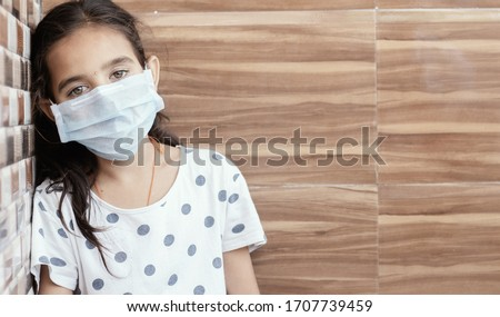 Concept of PTSD or post-traumatic stress disorder after covid-19 or coronavirus pandemic - Young teenager girl with medical mask wearing sat by leaning on well in sad, fear, or anxiety Royalty-Free Stock Photo #1707739459