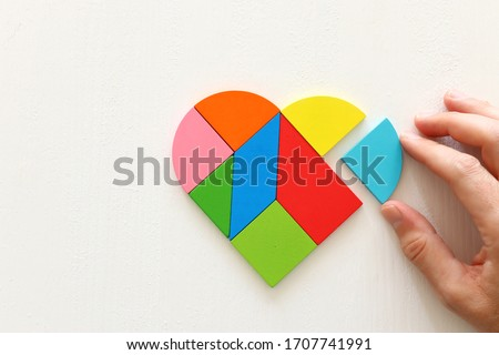 Heart puzzle on white wooden background