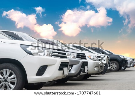 Cars park in asphalt parking lot in a row with cloudy sky background in nature. Outdoor parking lot with fresh ozone, green environment of transportation and technology concept  #1707747601