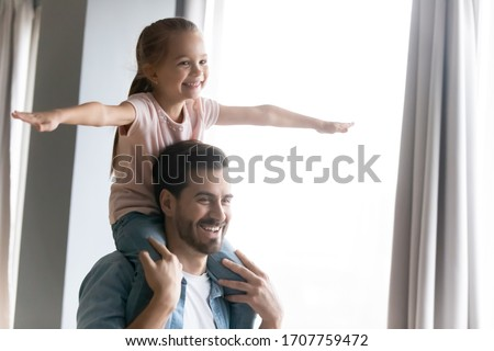 Father holding little cute daughter on shoulders having fun together at home, small adorable kid girl stretched arms imagines herself like a plane flying, funny activity with children indoors concept #1707759472
