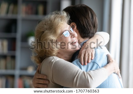 Loving elderly mother in glasses closed eyes enjoy moment strong cuddles adult son after long separation, grandmother glad to see grandson multi generational family reunion, love and bonding concept #1707760363