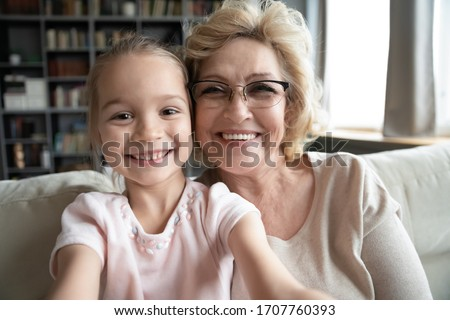 Old grandma in eyeglasses her little preschool granddaughter seated on sofa in living room holding cellular taking self-portrait picture, making video call webcam close up view faces, have fun concept
