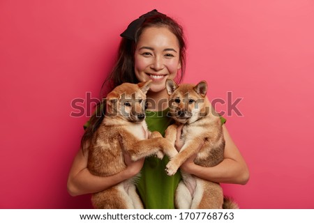 Happy brunette girl adopts two puppies from shelter, happy to have new friends, holds pets, being dog lover, going to walk. Animal owner suggests to adopt pet, smiles gladfully have friendly relations Royalty-Free Stock Photo #1707768763