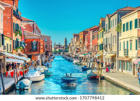 Murano islands, bridge across water canal, boats and motor boats, colorful traditional buildings, Venetian Lagoon, Veneto Region, Northern Italy. San Michele in Isola Catholic church background #1707798412