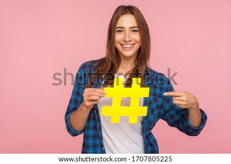 Attention to interesting blog post. Happy girl in shirt pointing at yellow hashtag symbol, making important topic popular, setting trends on Internet. indoor studio shot isolated on pink background Royalty-Free Stock Photo #1707805225