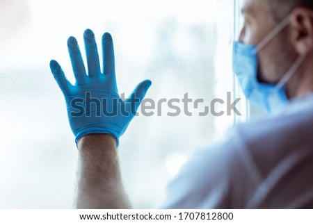 Self-Isolation. Sick Man Standing Near Window Looking Outside Wearing Medical Mask At Home During Coronavirus Quarantine. Selective Focus #1707812800