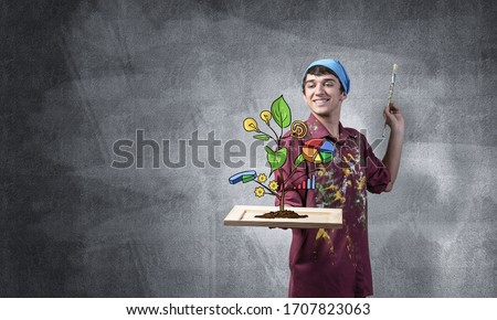 Young artist drawing plant of wealth and business success. Happy painter in dirty shirt and bandana standing on grey wall background. Original business idea generation and development. Royalty-Free Stock Photo #1707823063