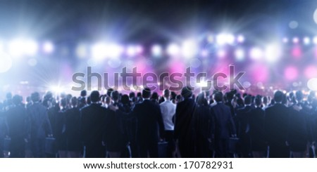 Crowd of businesspeople standing with back with lights at background #170782931