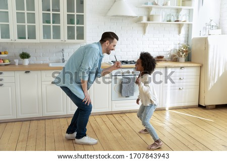 Happy young Caucasian father and little biracial daughter sing in kitchen appliances entertain at home, overjoyed dad and small African American girl child have fun play on weekend together #1707843943