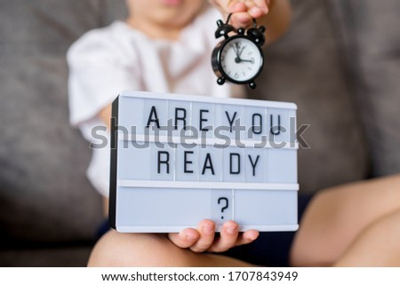 The boy is sitting on the couch holding an alarm clock, and the light box with the inscription you are ready. Concept #1707843949