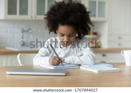 Smart little African American girl sit at desk in kitchen handwrite prepare homework or task, small biracial child study on quarantine at home, write in notebook, homeschooling, education concept #1707844027