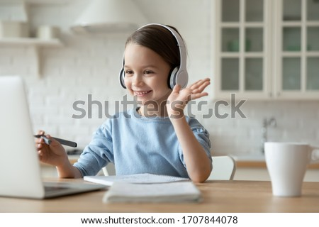 Smiling little Caucasian girl in headphones have video call distant class with teacher using laptop, happy small child wave greeting with tutor, study online on computer, homeschooling concept #1707844078