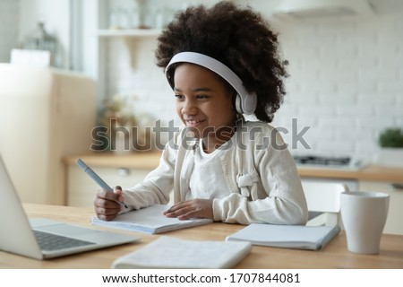 Smiling small African American girl in headphones watch video lesson on computer in kitchen, happy little biracial child in earphones have online web class using laptop at home, homeschooling concept #1707844081