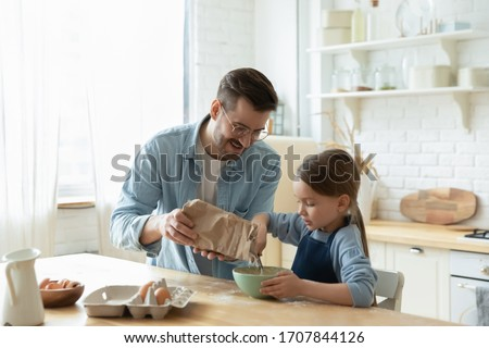 Caring young Caucasian father and cute little preschooler daughter bake in kitchen at home together, happy loving dad teach small girl child cooking, preparing pancakes or biscuits for breakfast #1707844126