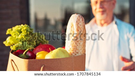 Close up of baguette and fresh vegetables in packet. Courier bringing food to old Caucasian man and handing outdoor. Deliveryman bringing grocery to male pensioner. #1707845134