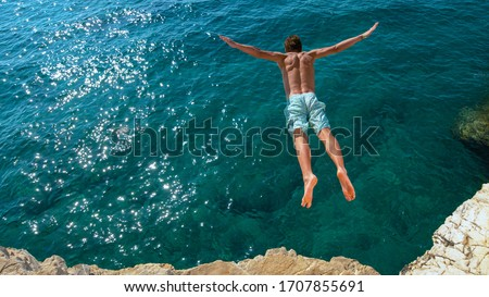 COPY SPACE: Young man on relaxing summer vacation does cliff diving on a hot and sunny day. Cinematic shot of an athletic Caucasian man jumping off a rocky ledge and into the glistening blue ocean. #1707855691