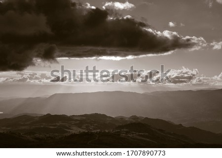 Cloudy mountains at sunset with beautiful light. Converted black and white. Toned.