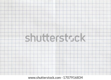 White checkered sheet of exercise book paper folded in two. White crumpled notebook paper texture background.