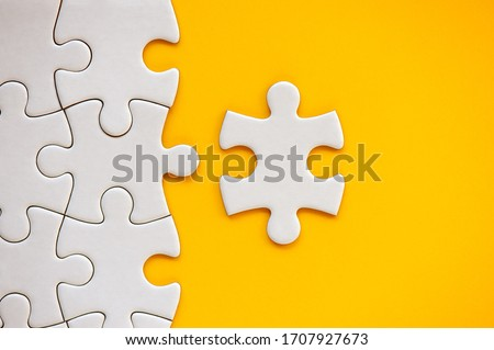 Puzzle pieces on orange background. White square puzzle pieces grid. Business background. Copy space for text, top view, close up. Royalty-Free Stock Photo #1707927673