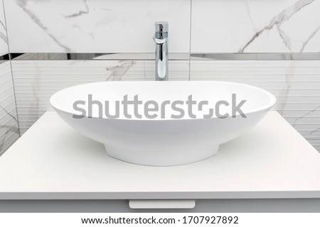 Modern white bathroom sink basin. Interior of bathroom with sink basin faucet. Modern design of bathroom. Modern hygienic wash basin. Clean hotel bathroom sink and faucet. #1707927892