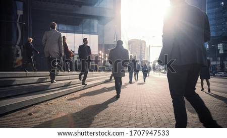 Office Managers and Business People Commute to Work in the Morning or from Office on a Sunny Day on Foot. Pedestrians are Dressed Smartly. Successful People Walking in Downtown. Cloudy Day in Downtown Royalty-Free Stock Photo #1707947533
