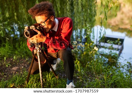 Young man as a nature photographer while filming or photographing in the countryside #1707987559