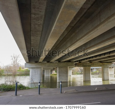Bottom view of the prestressed concrete beams and piers of Pont d'Empalot, a girder bridge in Toulouse, France, crossing the River Garonne and supporting the six-lane express way of Toulouse ring road #1707999160