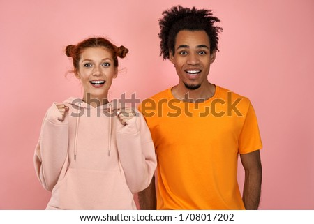 Photo of emotional ginger female and dark skinned male clench fists, exclaim and support favorite sports team, have overjoyed face expressions, dressed in casual wear, isolated on pink background. #1708017202