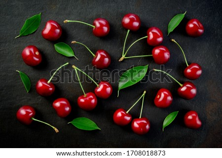 Cherries background. Cherries on black top view. Cherry background. Sour cherry with leaves on black background. #1708018873