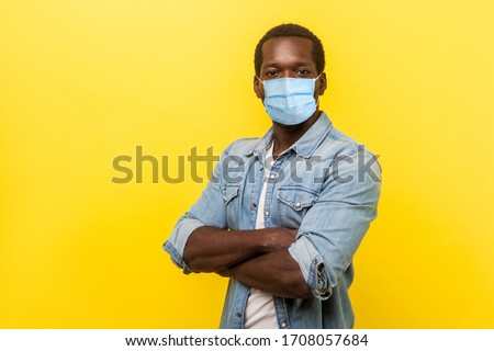 Portrait of man in casual shirt with surgical medical mask standing with crossed hands and looking at camera. medical and healthcare concept. indoor studio shot isolated on yellow background #1708057684