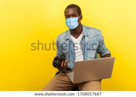 Portrait of energetic positive photographer with smile with surgical medical mask holding his camera and laptop, going to create video for blog. indoor studio shot isolated on yellow background