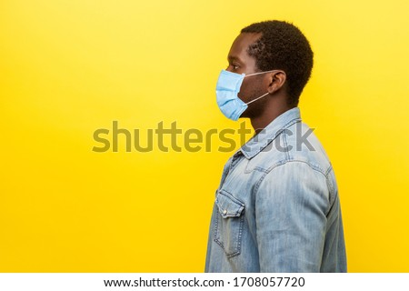 Profile portrait of serious young man with surgical medical mask looking left side with calm confident expression, blank copy space for text. indoor studio shot isolated on yellow background Royalty-Free Stock Photo #1708057720