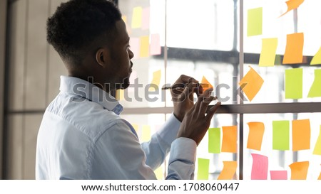 Focused African American male employee write on colorful sticky notes develop business project in office, concentrated biracial man worker brainstorm engaged in creative thinking make startup plan Royalty-Free Stock Photo #1708060447
