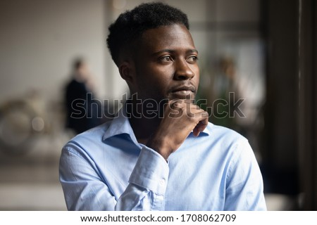 Pensive African American male employee look in distance thinking planning or visualizing, thoughtful biracial businessman lost in thoughts pondering over problem solution, business vision concept Royalty-Free Stock Photo #1708062709