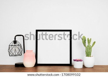 Mock up black square frame with home decor and potted plants. Wooden shelf against a white wall. Copy space.