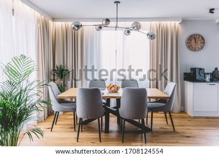 Dining room with wooden table and floor in modern apartment. Interior design Royalty-Free Stock Photo #1708124554