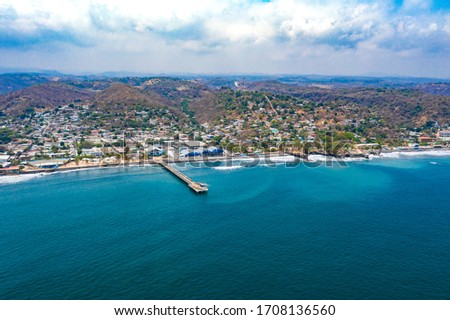 Aerial view over the coastal area on La Libertad beach in El Salvador, where you can see in its entirety its pier and the turquoise sea water. #1708136560